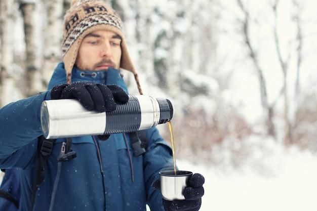 Homem bonito alpinista em roupas quentes derrama chá em caneca de garrafa térmica na floresta de inverno.