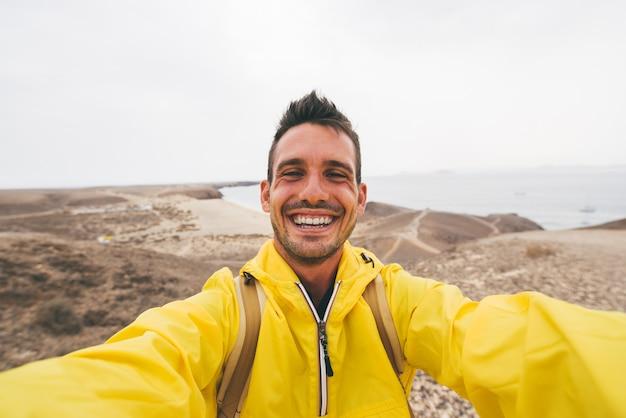 Homem bonito alpinista sorrindo tomando uma selfie no topo de uma montanha.