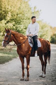 Homem bonito andando a cavalo na floresta