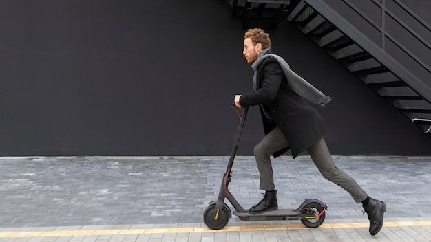 Homem bonito andando de scooter elétrica