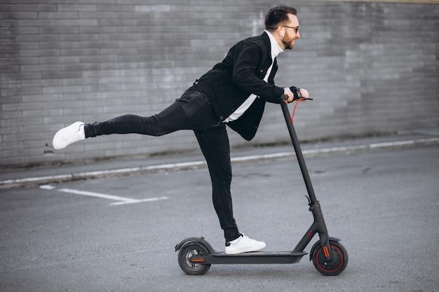 Homem bonito andando na cidade de scooter