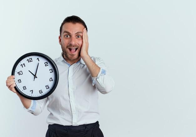Homem bonito animado coloca a mão no rosto segurando um relógio isolado na parede branca