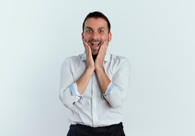 Homem bonito animado colocando as mãos no rosto isolado na parede branca