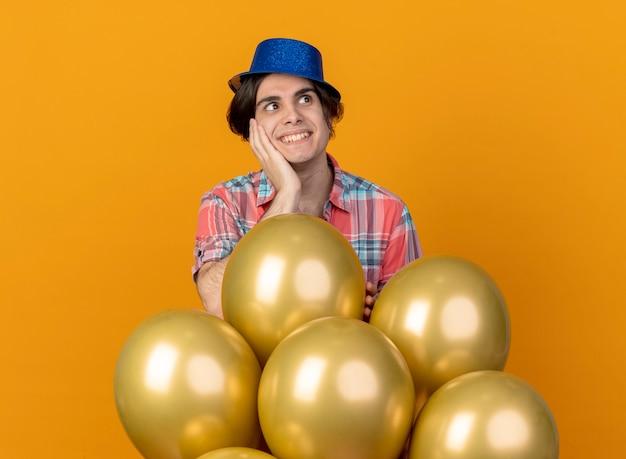 Homem bonito animado com chapéu de festa azul coloca a mão no rosto e fica de pé com balões de hélio olhando para o lado isolado na parede laranja
