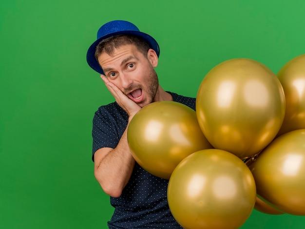 Homem bonito animado com chapéu de festa azul coloca a mão no rosto e segura balões de hélio isolados na parede verde