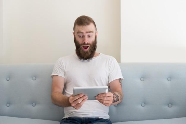 Homem bonito animado com tatuagem assistindo vídeo no tablet