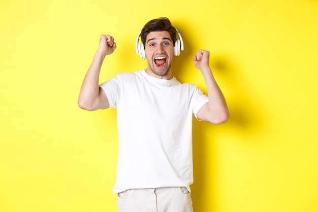 Homem bonito animado dançando e cantando junto, ouvindo música em fones de ouvido, em pé sobre a parede amarela
