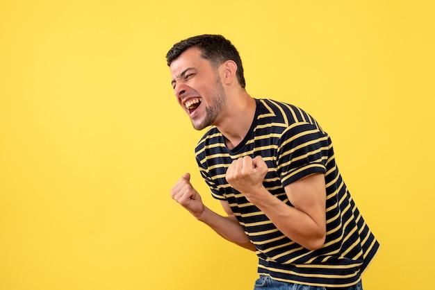 Homem bonito animado de vista frontal em uma camiseta listrada em preto e branco, mostrando o gesto vencedor em um fundo amarelo isolado