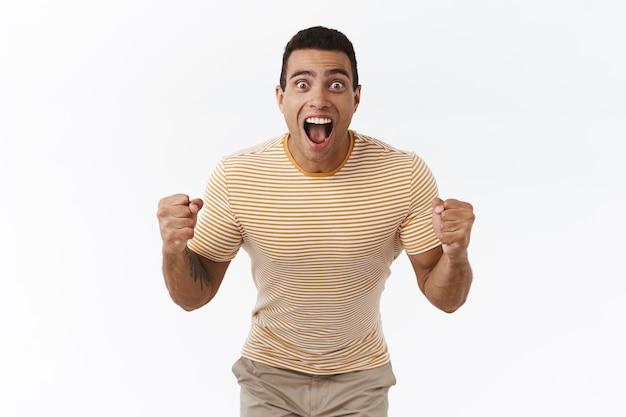 Homem bonito animado e animado ganhando muito dinheiro, olhando para um placar ou uma partida esportiva com felicidade