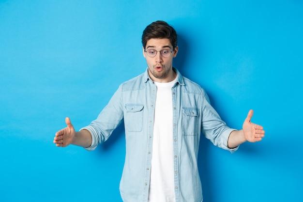 Homem bonito animado mostrando um objeto de tamanho grande e parecendo surpreso, de pé sobre um fundo azul