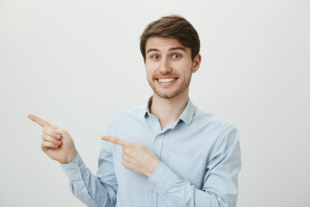 Homem bonito animado, sorrindo amplamente, apontando o dedo para a esquerda para o banner promocional