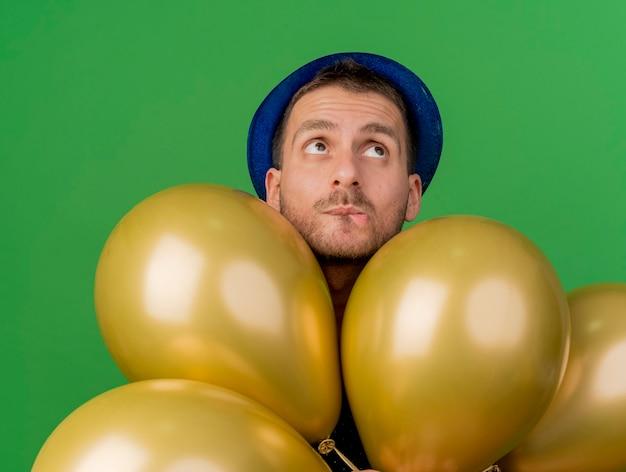 Homem bonito ansioso com chapéu de festa azul segurando balões de hélio olhando para cima, isolados na parede verde
