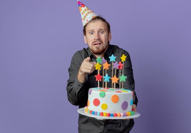 Homem bonito ansioso com um boné de aniversário segurando um bolo e apontando para a frente, isolado na parede roxa
