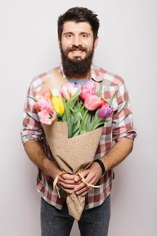 Homem bonito apaixonado, desejando feliz dia dos namorados, dando buquê de flores em um encontro romântico, sorrindo, vestindo terno sobre parede branca