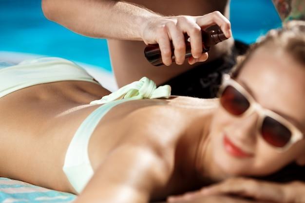 Homem bonito, aplicar creme bronzeador na mulher perto da piscina