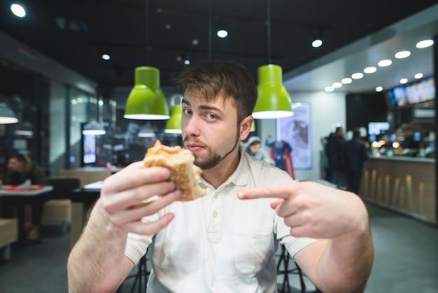 Homem bonito aponta o dedo para o hambúrguer na mão