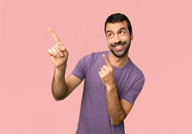 Homem bonito, apontando com o dedo indicador e olhando no fundo rosa isolado