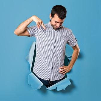 Homem bonito apontando para baixo através de um buraco de papel