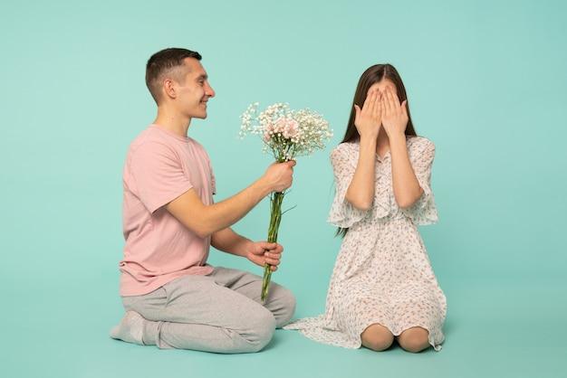 Homem bonito, apresentando flores da primavera para sua linda namorada que esconde o rosto com as mãos e à espera de surpresa