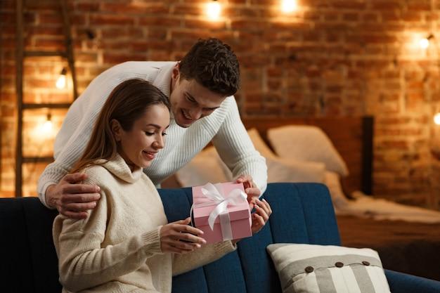 Homem bonito apresentando um presente para sua linda garota e sorrindo