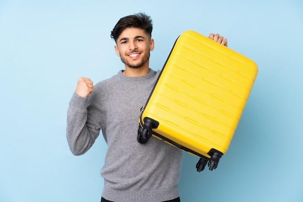 Homem bonito árabe na parede azul em férias com mala de viagem