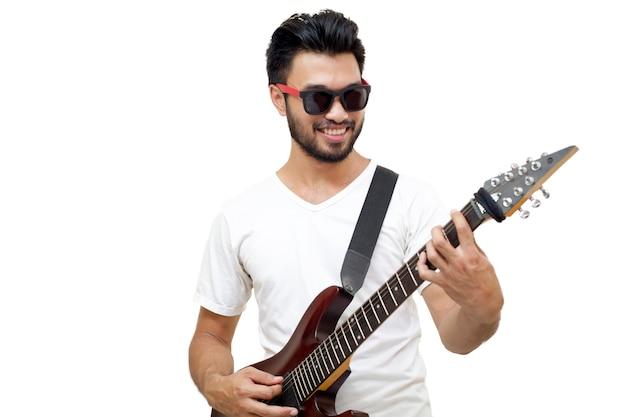 Homem bonito asiático com um bigode, sorrindo e rindo, tocando guitarra isolada em background branco