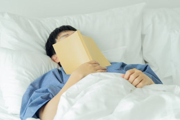 Homem bonito asiático leia livros enquanto dorme