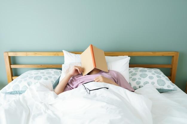 Homem bonito asiático ler livros enquanto dorme. capa de livro do homem a sonolência causa sono.
