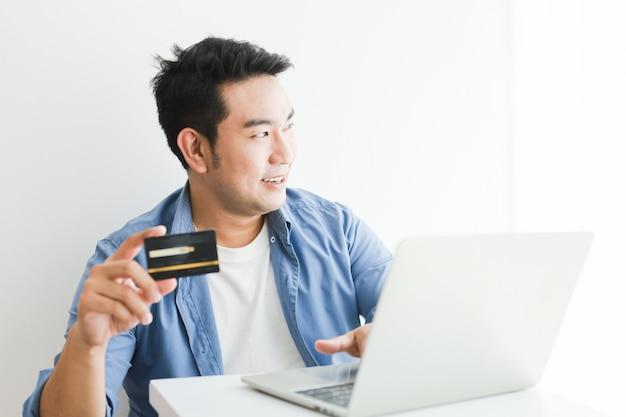 Homem bonito asiático na camisa azul usando cartão de crédito com o computador portátil, compras on-line