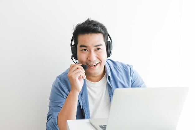 Homem bonito asiático na camisa azul usando laptop com fone de ouvido falando sorriso e cara feliz