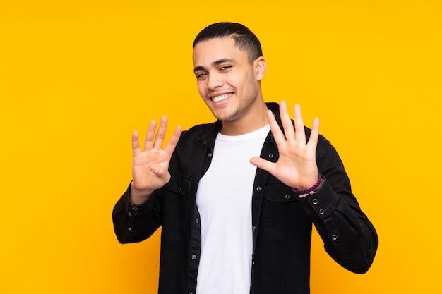 Homem bonito asiático na parede amarela, cobrindo os olhos pelas mãos e sorrindo