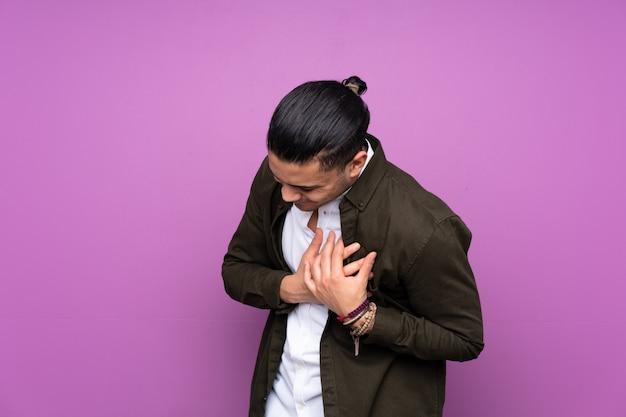 Homem bonito asiático na parede azul com uma dor no coração