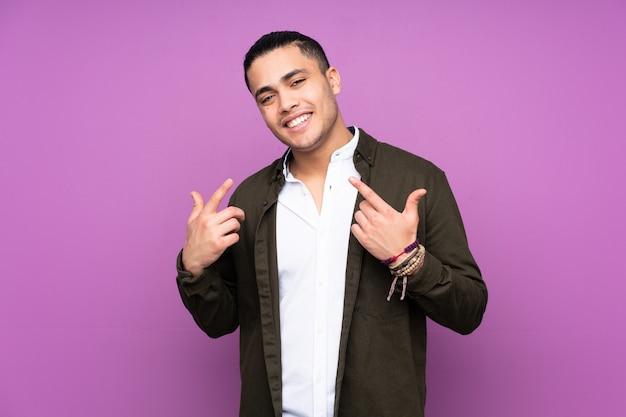 Homem bonito asiático na parede azul, dando um polegar para cima gesto