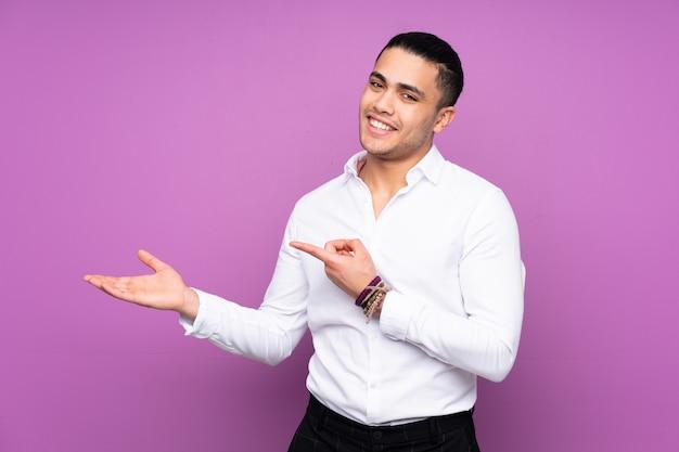 Homem bonito asiático na parede azul, segurando o espaço em branco imaginário na palma da mão