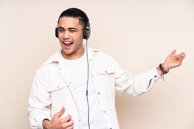 Homem bonito asiático na parede bege, ouvindo música e fazendo gesto de guitarra