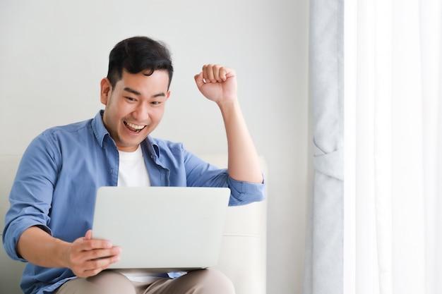 Homem bonito asiático que trabalha com o computador portátil na sala de estar feliz e sorriso rosto