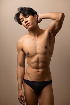 Homem bonito asiático sem camisa no quarto