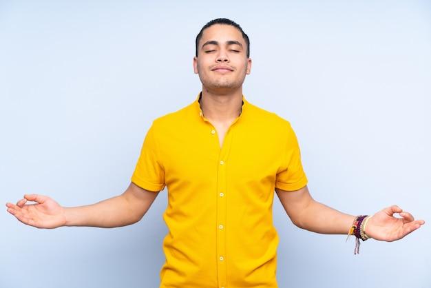 Homem bonito asiático sobre fundo isolado em pose zen
