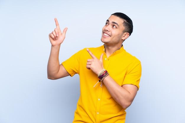 Homem bonito asiático sobre parede apontando com o dedo indicador uma ótima idéia