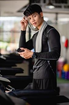 Homem bonito asiático vestindo roupas esportivas e smartwatch, descansando na esteira, usando uma toalha, enxugando o suor na testa e segurando o smartphone após o treino na academia moderna,