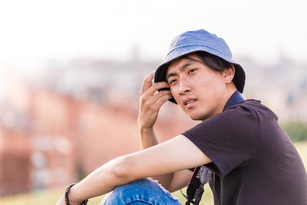 Homem bonito asiático viajando com uma câmera