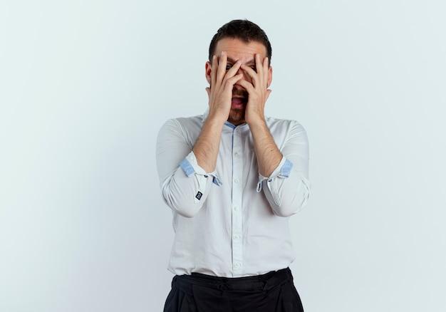 Homem bonito assustado fecha o rosto com as mãos olhando através de dedos isolados na parede branca