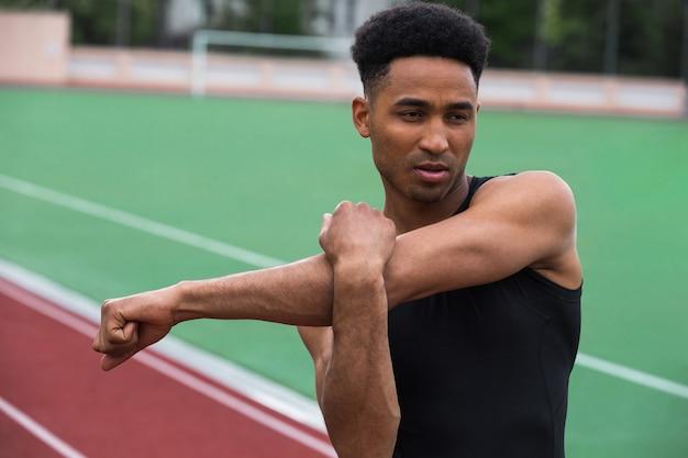 Homem bonito atleta africano fazer exercícios de alongamento