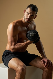 Homem bonito atleta de short preto começando a treinar na academia com kettlebell isolado em