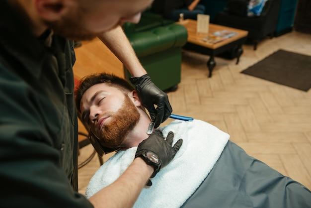 Homem bonito, barbear-se barbear por cabeleireiro enquanto está na cadeira de barbearia.