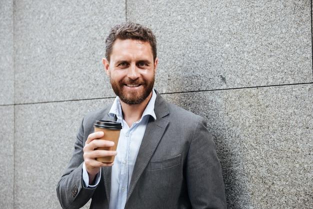 Homem bonito barbudo de terno cinza e camisa branca encostado na parede de granito e sorrindo enquanto bebe café para viagem
