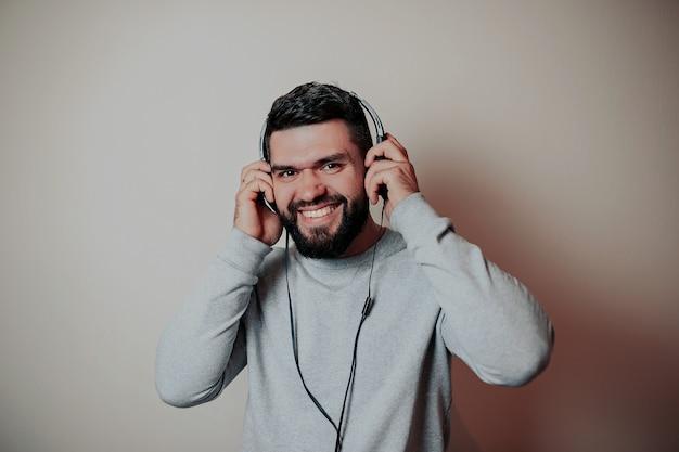 Homem bonito barbudo em fones de ouvido, homem ouvindo música