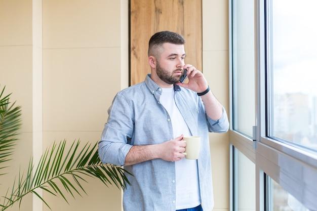 Homem bonito barbudo fica ao lado da janela com uma xícara na mão na varanda e bebe um café ou chá quente homem com roupas casuais aprecia a vista no escritório ou em casa relaxando ou dando um tempo no trabalho