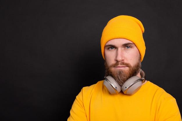 Homem bonito barbudo hippie chapéu amarelo camiseta com fones de ouvido isolados no fundo preto