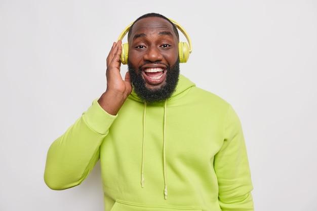 Homem bonito barbudo hippie com pele escura curtindo playlists favoritas gosta de ouvir música mantém a mão em fones de ouvido sem fio sorrisos amplamente vestido com capuz verde isolado sobre a parede branca